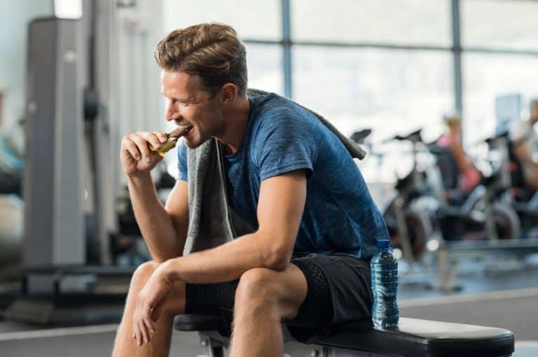 Homem sentando em aparelho de academia comendo barra de proteína