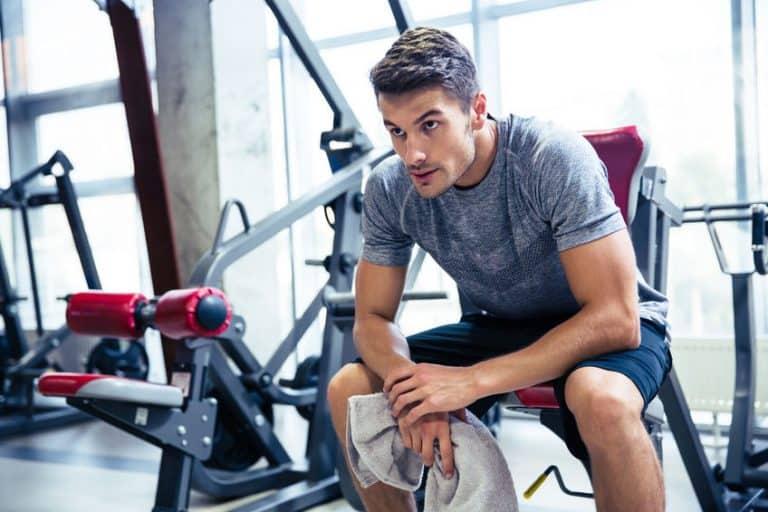 Homem sentado em aparelho de academia segurando uma toalha