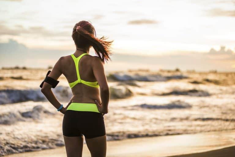 Mulher com roupa de ginástica observa a praia