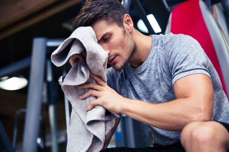 Homem na academia secando o suor do rosto com uma toalha