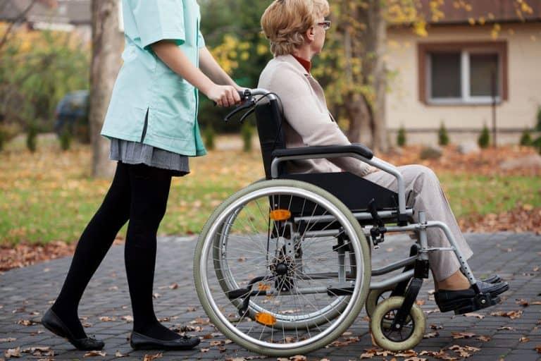 Enfermeira empurrando cadeirante pela rua
