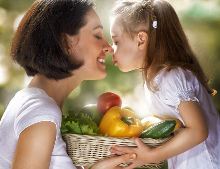 Imagem mostra uma mulher e uma menina segurando uma cesta de verduras