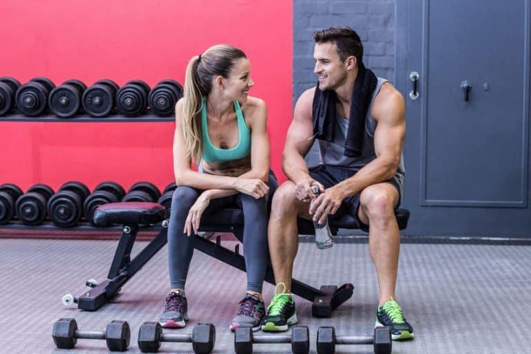 Homem e mulher conversam sentados em um banco de academia