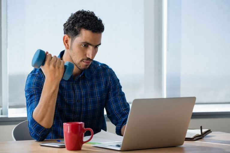 Homem se exercita com peso enquanto trabalha no computador
