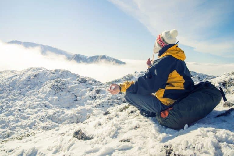 Homem meditando sentado no topo de uma montanha