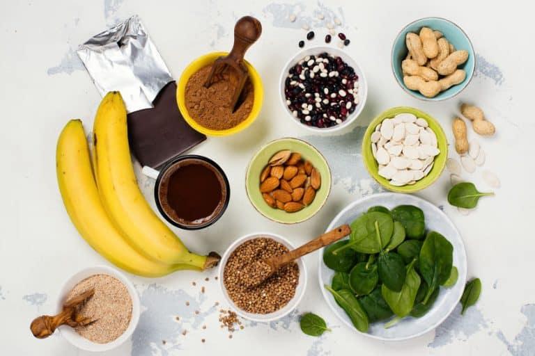 Mesa repleta de alimentos ricos em magnésio, como banana, cereais e folhas