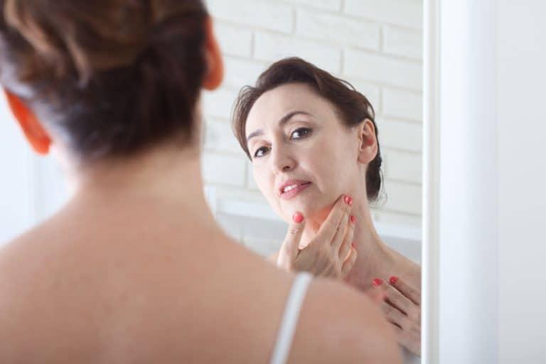 Mulher se observa no espelho
