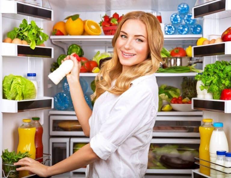 Mulher retirando vidro de iogurte da geladeira