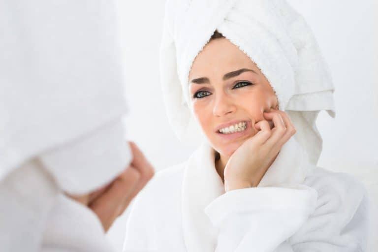 Mulher de roupão branco se olhando no espelho