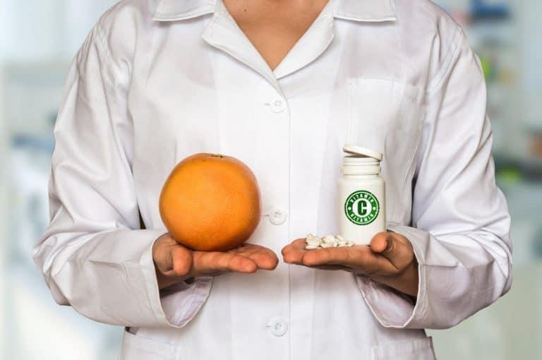 Farmacêutico segurando exemplos de vitamina C.