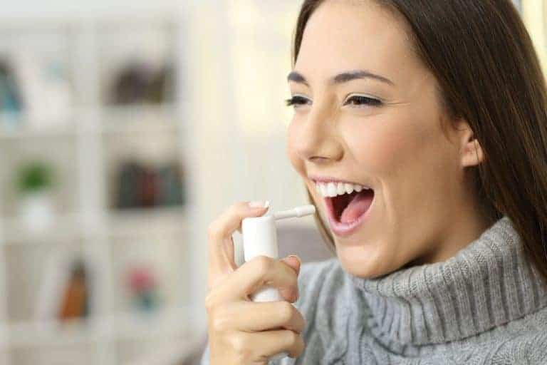 Imagem de mulher aplicando spray na boca.