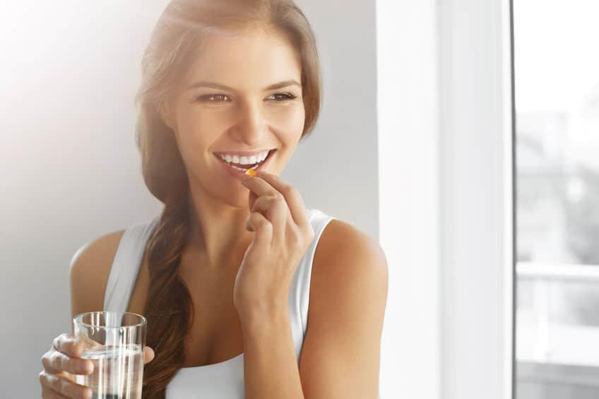 mulher tomando suplementos de zinco