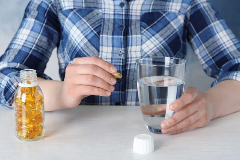 Imagem de pessoa tomando comprimido.
