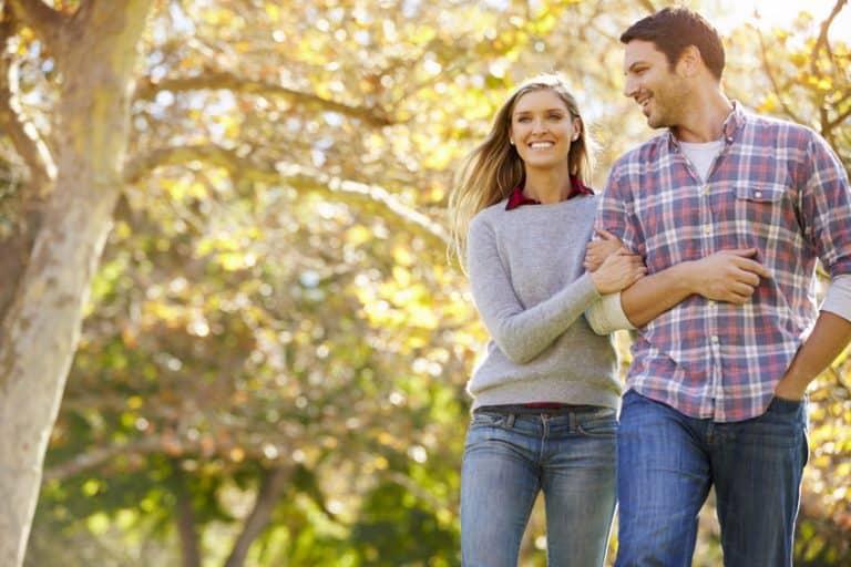 Imagem de casal de braços dados, caminhando.