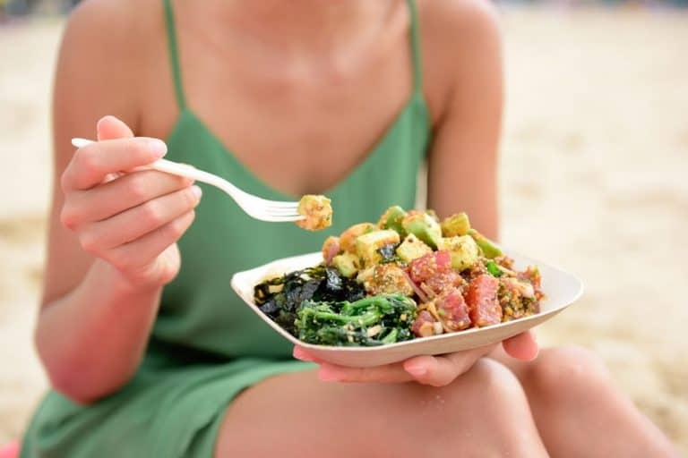 Mulher sentada comendo salada.