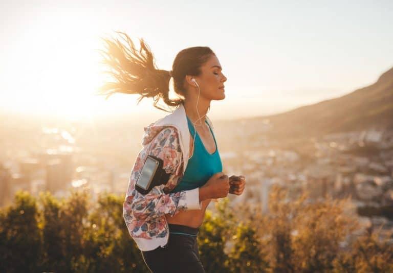 Imagem de mulher correndo em dia ensolarado.