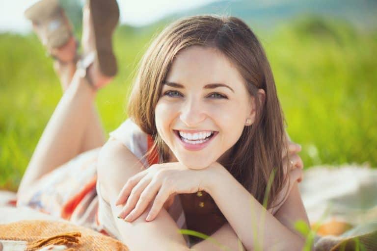 Imagem de mulher em parque sorrindo.
