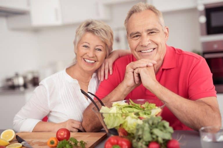 Imagem de casal de idosos preparando salada.
