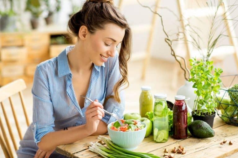 Mulher sentada na mesa comendo salada.