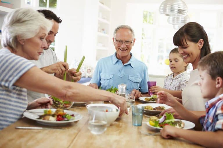 Imagem de família na mesa comendo.