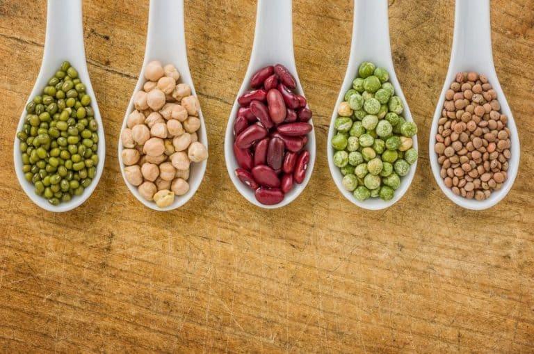 Imagem de grãos de ervilha e outras sementes em colher.