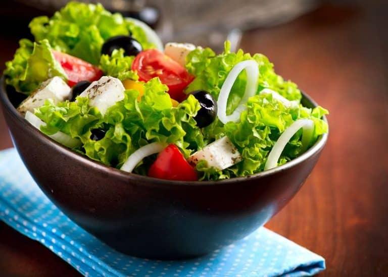 Imagem de pote com salada de alface, tomate e cebola.