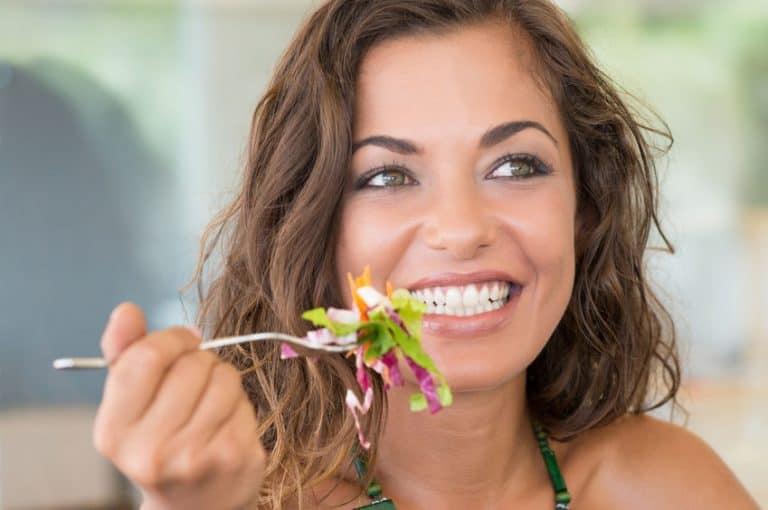 Imagem de mulher comendo salada.