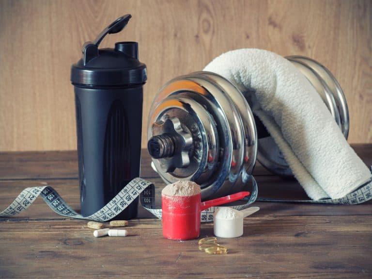 Coqueteleira, suplementos, toalha e peso de academia.