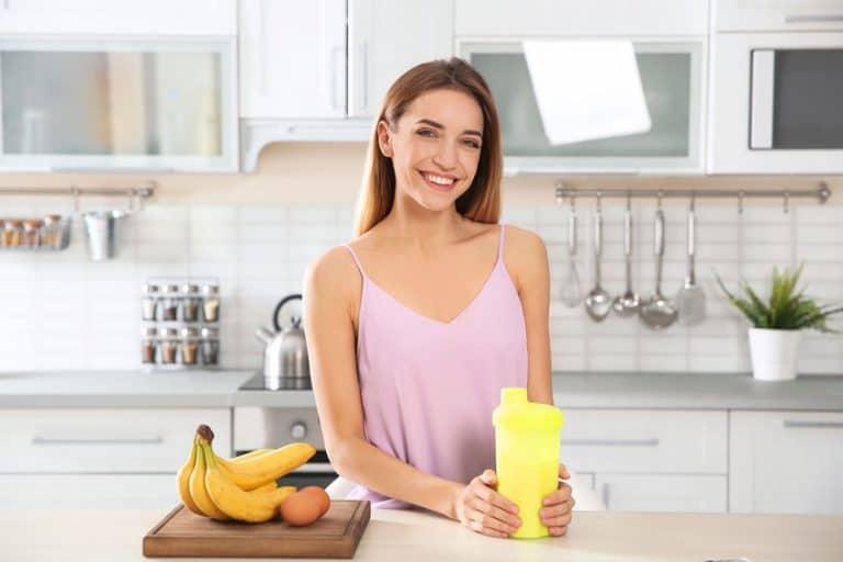 Mulher segurando seu shake de whey.