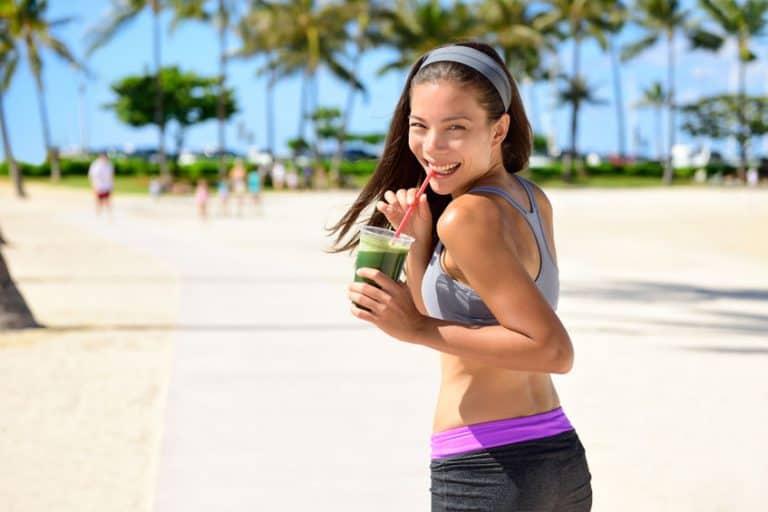 Mulher correndo com suco verde.