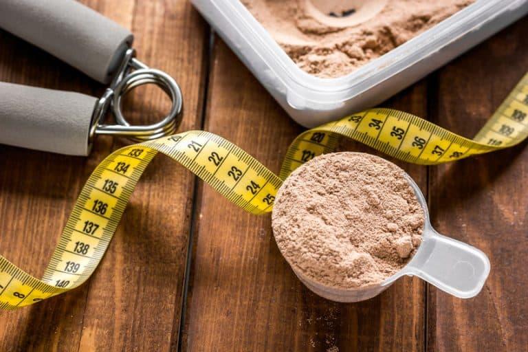 Pote com whey protein e fita métrica.