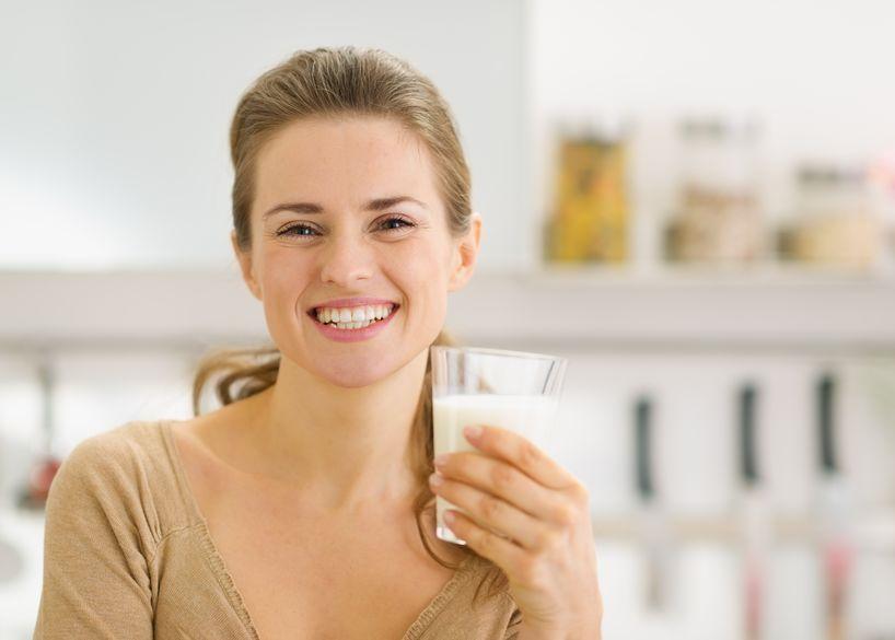 menina sorridente, bebendo leite de soja