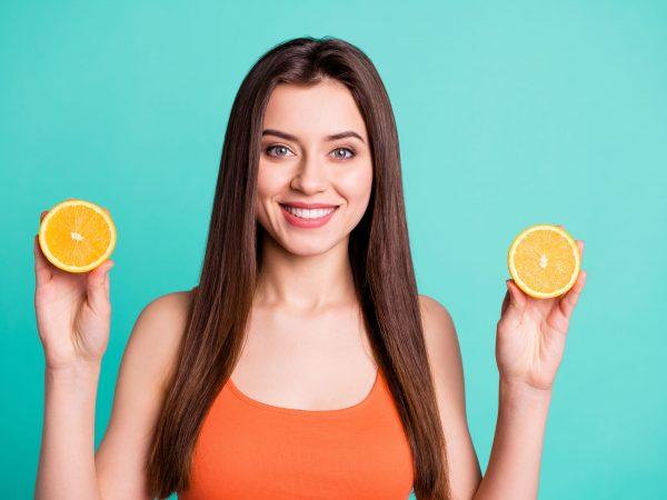 Mulher segurando fatias de laranja