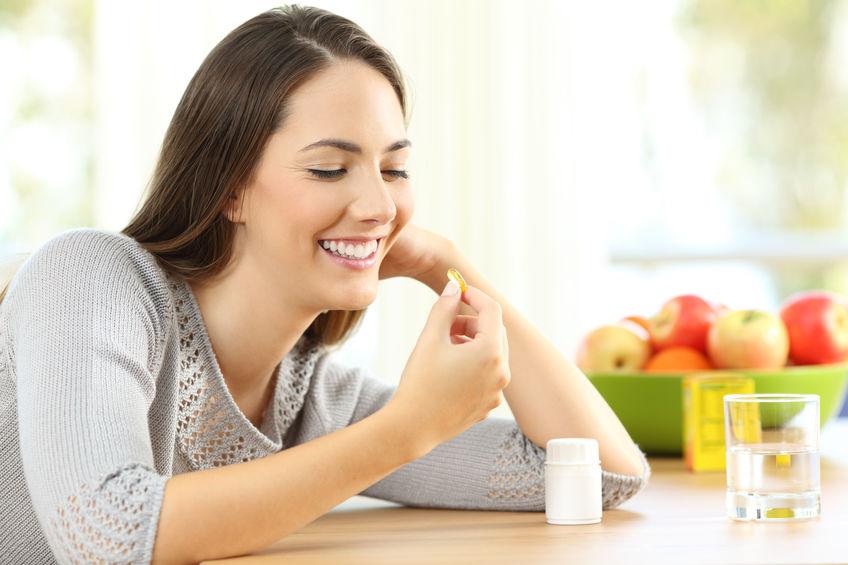 Imagem de mulher tomando cápsula de vitamina.