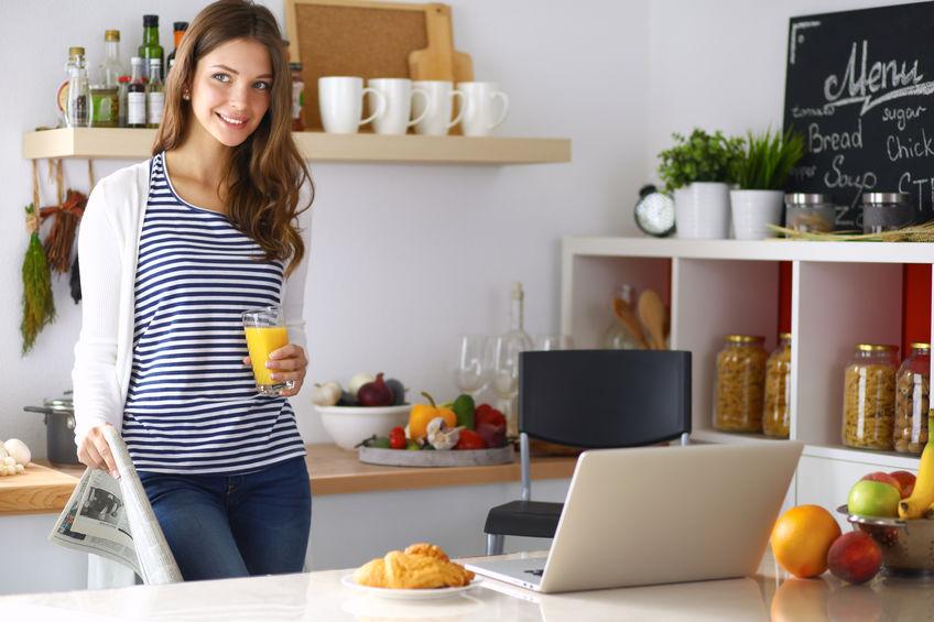 Mulher na cozinha com copo de suco de laranja na mão no laptop na mesa