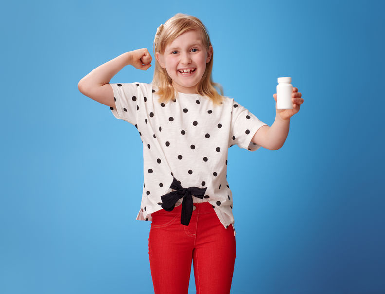 girl showing bottles of vitamins and biceps gesture on blue