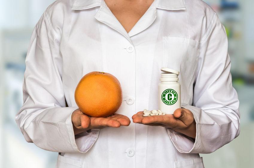 médica segurando uma laranja na mão direita e um frasco de vitamina C na mão esquerda