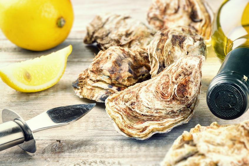 Imagem de ostras, limão e vinho branco sobre mesa.