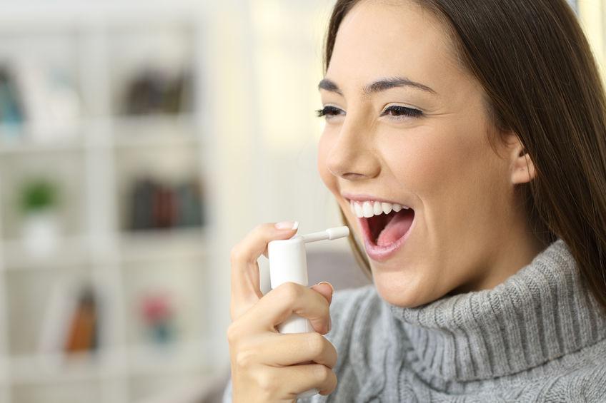 Maglia da portare della donna felice facendo uso di uno spruzzo analgesico per ammorbidire la gola che si siede su un sofà in un interno della casa