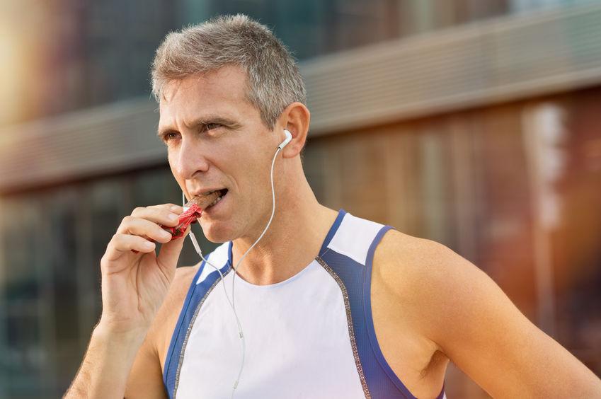 homem no ginásio comendo barra de proteína