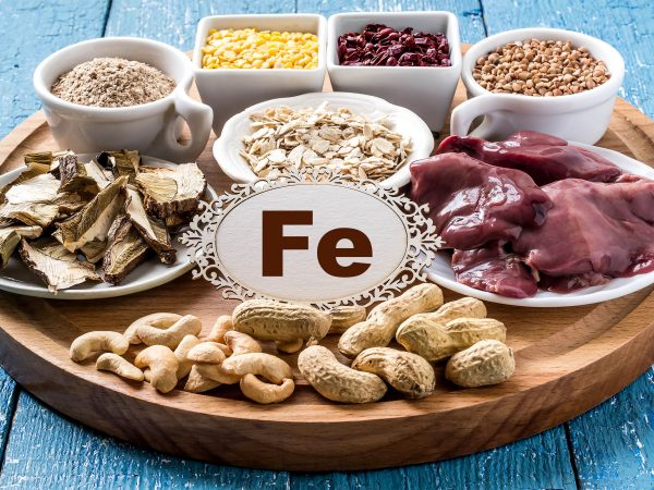 Products containing ferrum (dried mushrooms, bran, buckwheat, livers, dogwood, cashews, oats, lentils, peanuts) on a round cutting board and a blue wooden background