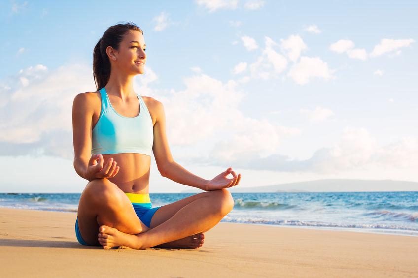 menina meditando na praia