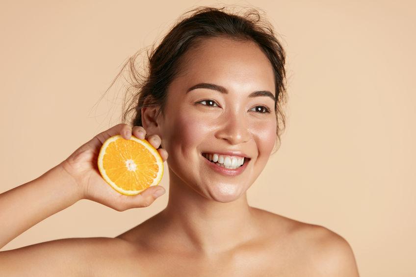 menina com uma laranja ao lado