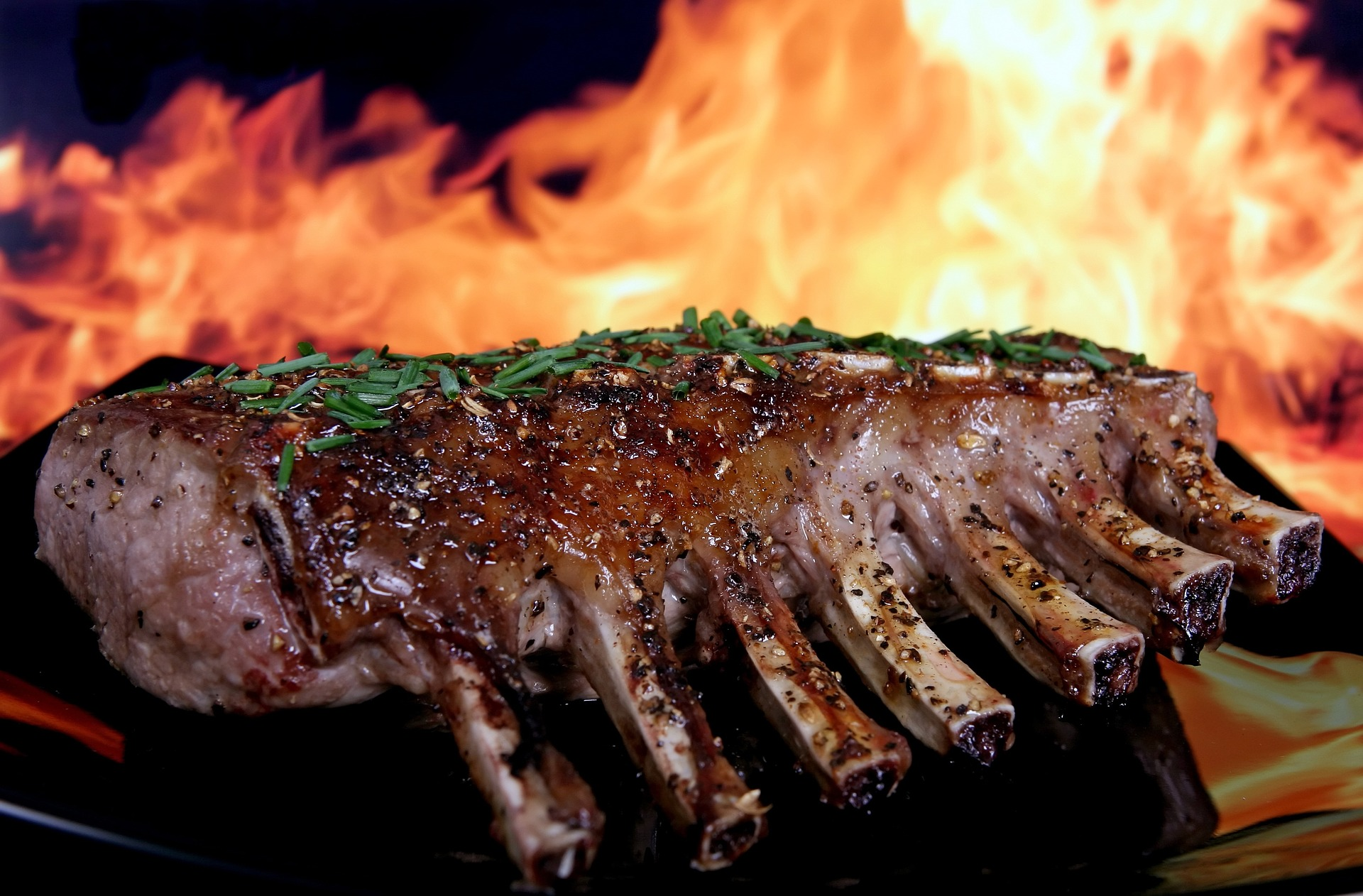 Costela de porco com chama de fogo ao fundo.