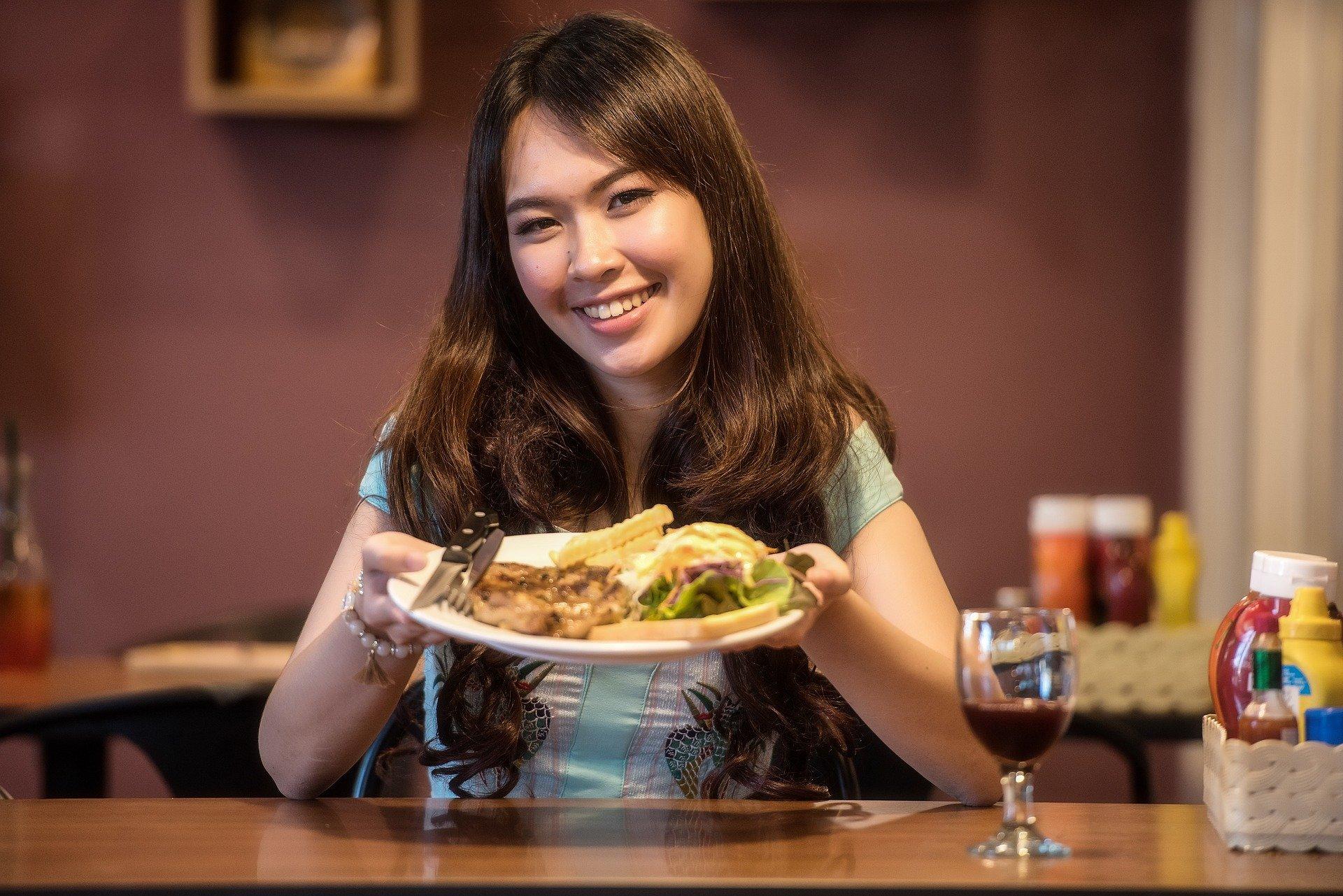Mulher segurando prato de comida.