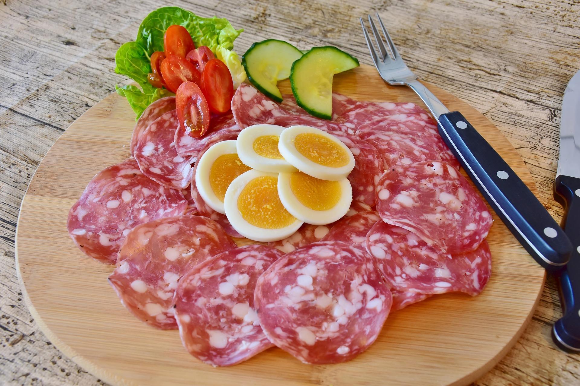 Fatias de salaminho, ovo, pepino, tomate, alface e um garfo sobre uma tábua redonda de madeira.