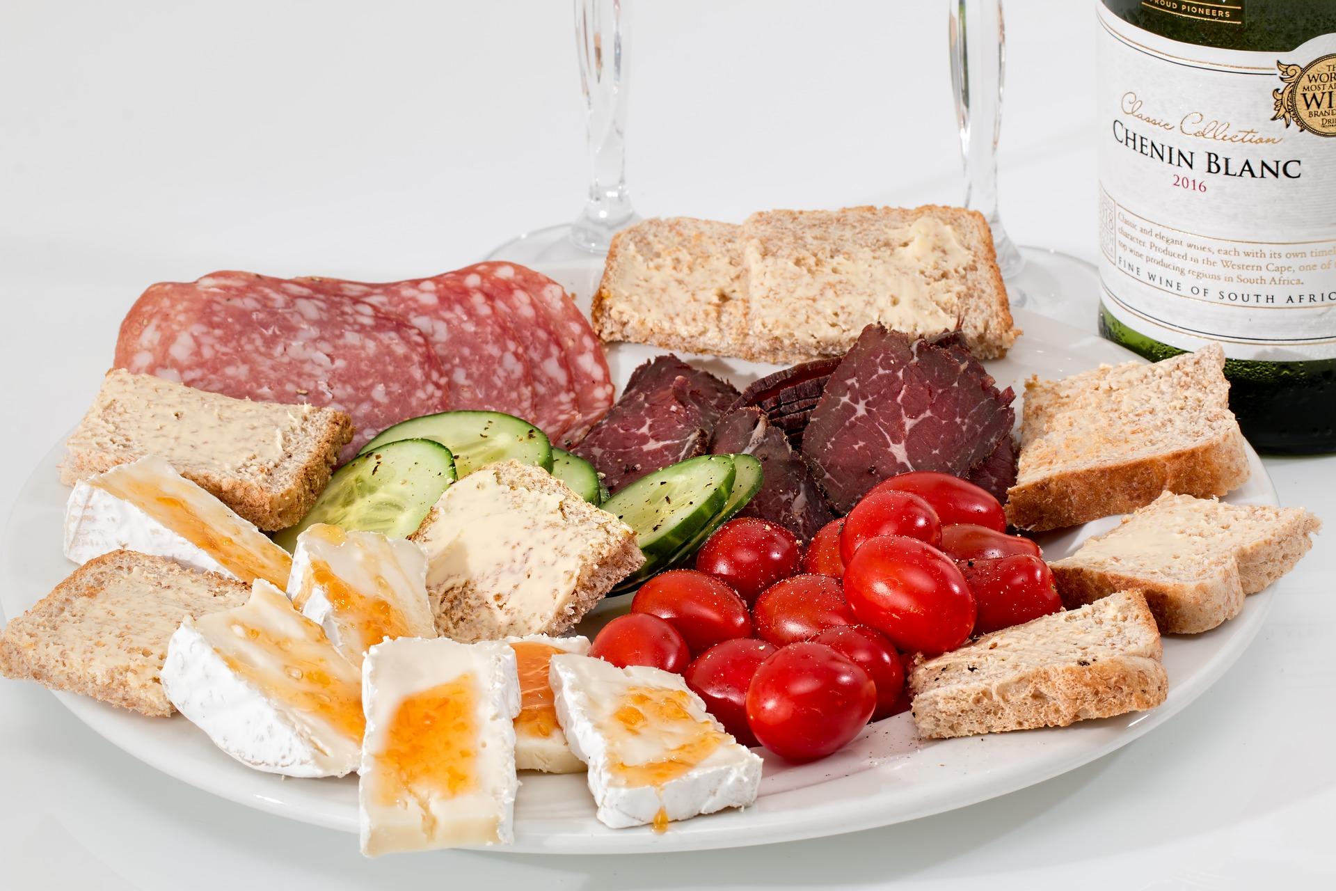 Prato com salame, ovos, pães e tomates.