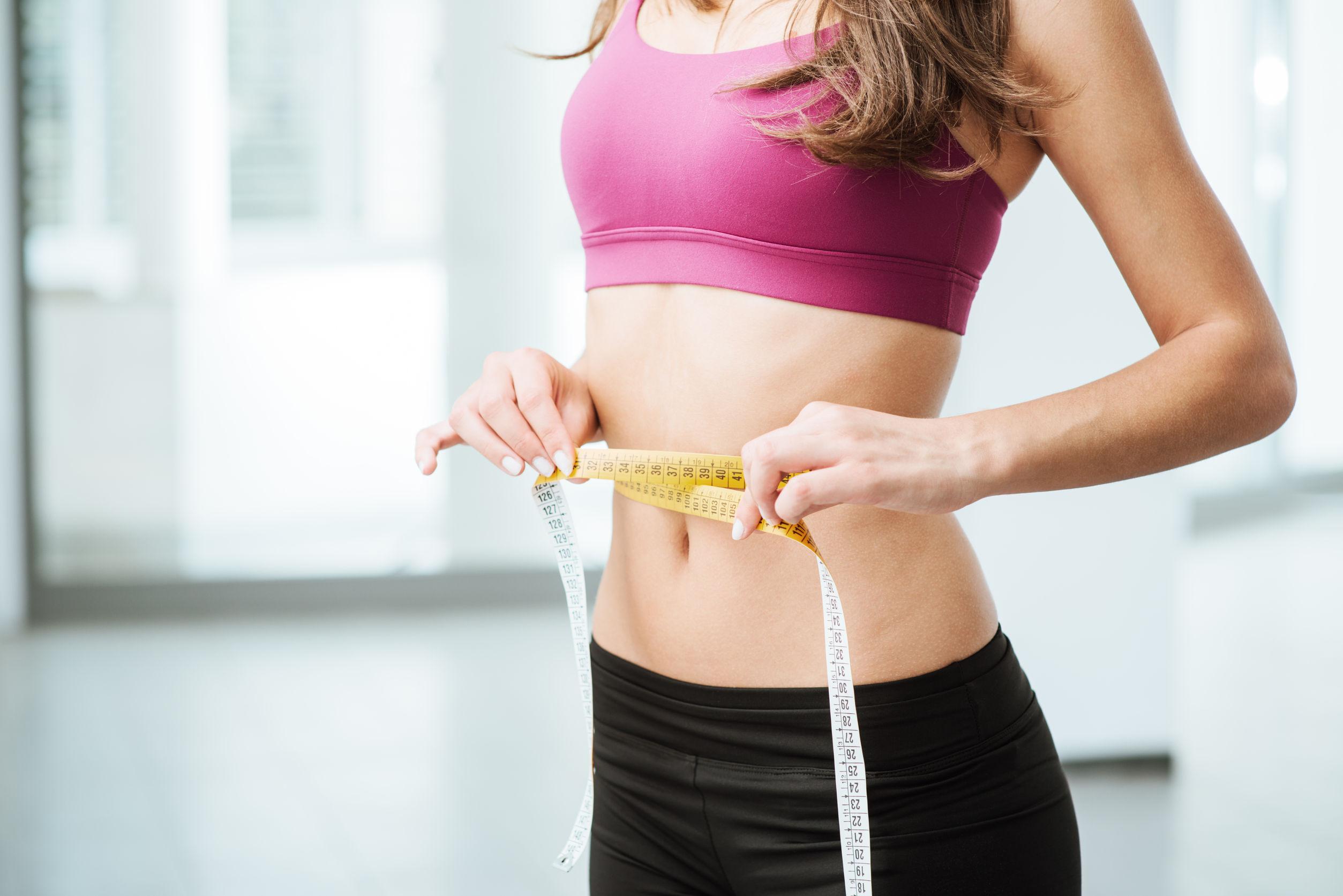 Imagem de uma mulher medindo a circunferência da barriga.