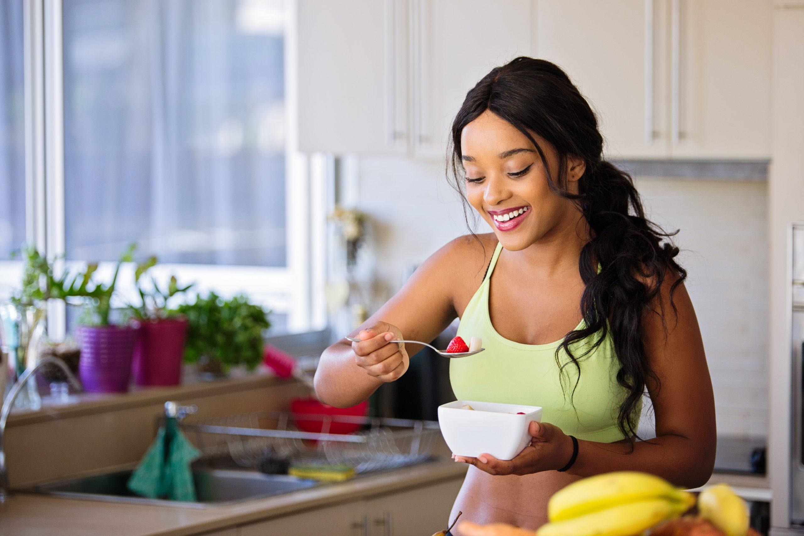Imagem de uma mulher comendo frutas.