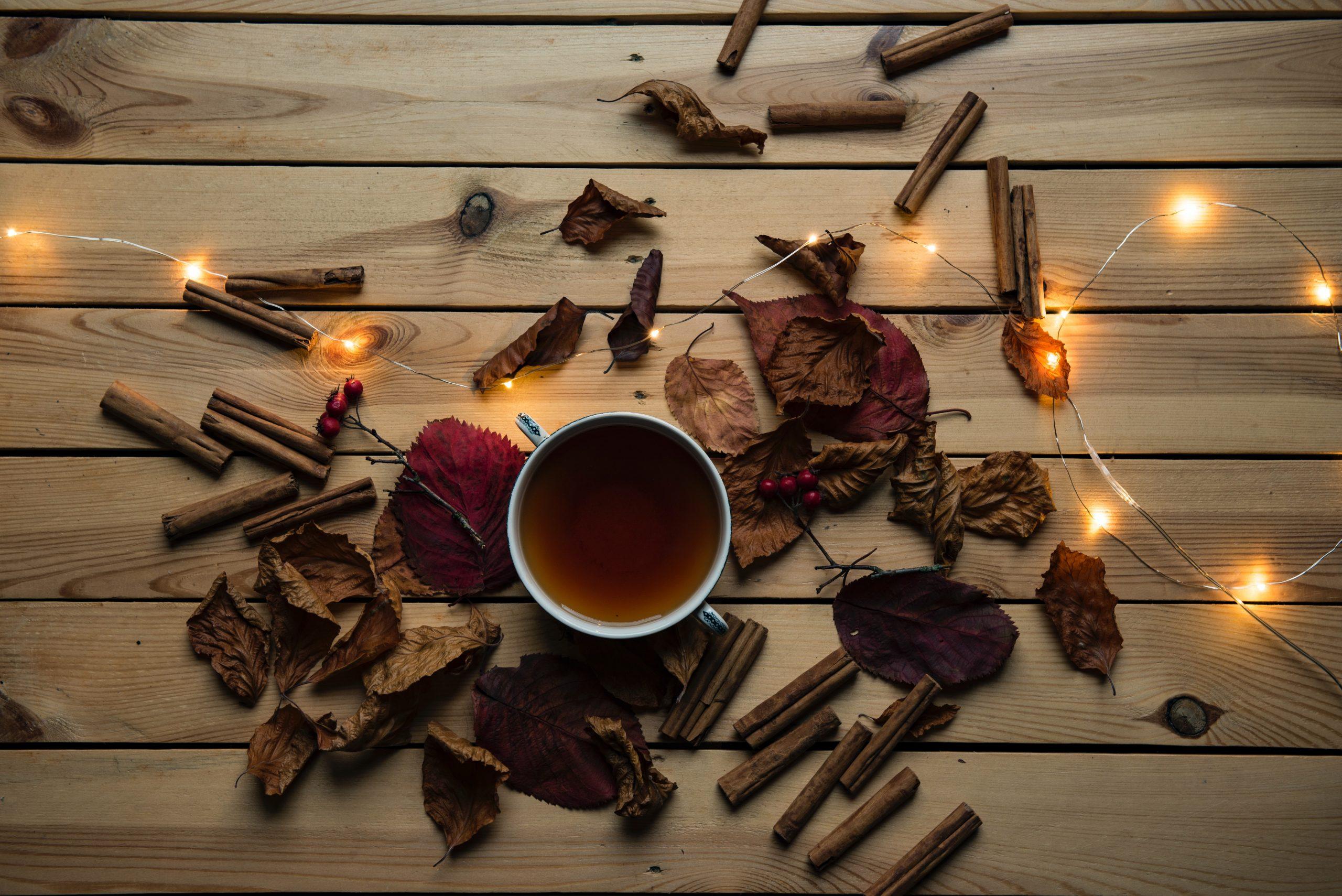 Imagem de uma xícara de chá vista de cima sobre tábua de madeira ao lado de folhas e pau de canela.